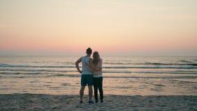 Att älska par är omfamna och se vattenhavsvågor på solnedgången i sommar lager videofilmer