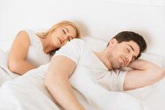 Att älska par ligger i säng som inomhus hemma sover arkivbilder