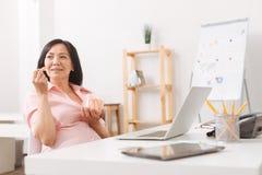 Att äta för gravid kvinna behandla som ett barn moroten i kontoret Arkivbilder
