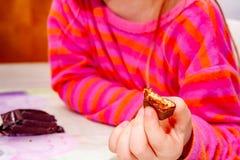 Att äta för liten flicka flinar chokladstången för frukost royaltyfria bilder
