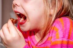 Att äta för liten flicka flinar chokladstången för frukost royaltyfri foto