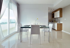 Att äta middag tabellen med tabellen ställde in i den vita lyxiga moderna bosatta interien royaltyfria foton
