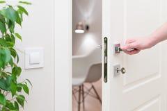 Att att öppna dörren Modern vit dörr med krommetallhandtaget och en arm för man` s Royaltyfri Fotografi