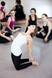 Att öva för yogiflicka som gör yogakamlet, poserar i grupp Arkivbilder