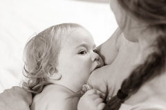 Att amma behandla som ett barn Ståendemamman och behandla som ett barn att amma Royaltyfri Fotografi
