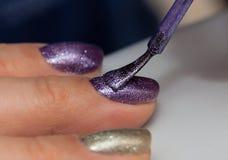 Att applicera stelnar spikar polermedel på spikar av fingrarna Royaltyfri Bild