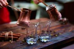 Att att hälla arabiskt kaffe i koppar på träbakgrund Arkivbilder