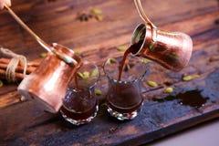 Att att hälla arabiskt kaffe i koppar på träbakgrund Royaltyfria Bilder
