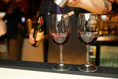 Att att hälla två exponeringsglas av vin på stången Royaltyfri Bild