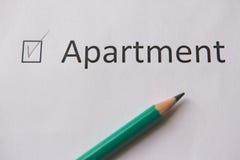 Att att köpa en lägenhet ordet LÄGENHET är skriftligt på vitbok med fästingen, och grå färger ritar Royaltyfri Fotografi