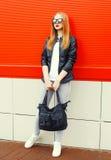 Att bära för modekvinna vaggar det svarta omslaget, solglasögon och påsen över rött Royaltyfri Foto