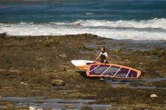 Att bära för surfare som är hans, vindsurfar brädet Royaltyfri Foto