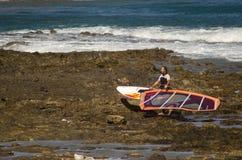Att bära för surfare som är hans, vindsurfar brädet Arkivfoton