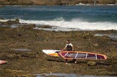 Att bära för surfare som är hans, vindsurfar brädet Royaltyfri Bild