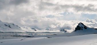 Att bölja fördunklar över snö-täckte berg och isberg, den Livingstone ön, antarktisk halvö arkivbild