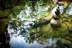 Att balansera vaggar tornet för zenmeditationövning mot bakgrund field blåa oklarheter för grön vitt wispy natursky för gräs Arkivbilder