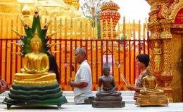 Att be för folk toGolden Buddhastatyn i buddistisk tempel Arkivfoto