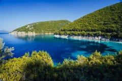 Att bedöva sjösidalandskap av lilla viken med vatten för det lugna havet för turkos som omges av kullar som är bevuxna med, sörje royaltyfri fotografi