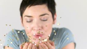Att blåsa för kvinna som är guld-, mousserar ut ur hennes händer i ultrarapid stock video