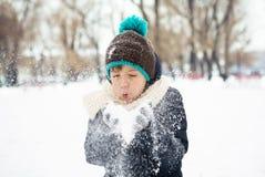 Att blåsa för pojke som är insnöat dentäckte kalla vintern, parkerar Arkivfoto