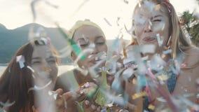 Att blåsa för tre vänkvinnor som är färgglat, blänker på stranden på solnedgången stock video