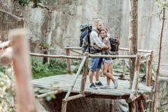 Att bry sig älska mannen som kramar hans kvinna, medan bära ryggsäckar och fotvandra fotografering för bildbyråer
