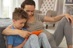 Att bry sig älska modern som kramar hennes smarta pojke Arkivbild