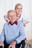 Att bry sig den handikappade patienten för doktorsportion Arkivbild