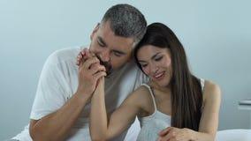 Att bry sig den kyssande fruarmen för maken i säng, daterar vänner, familjförälskelse, vilar hemma stock video