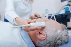 Att bry sig den medicinska specialisten som ger den head ultraljudet i sjukhuset Fotografering för Bildbyråer