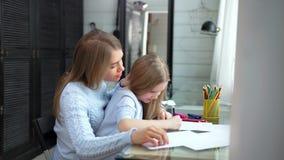 Att bry sig den unga modern som hjälper den lilla dotterteckningsbilden genom att använda medelskottet för färgrik blyertspenna arkivfilmer