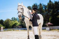Att bry sig denhaired kvinnliga ryttaren som ser hennes favorit- tävlings- häst fotografering för bildbyråer