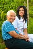 Att bry sig doktor med den sjuka gammalare kvinnan utomhus Royaltyfria Foton