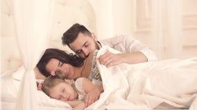 Att bry sig fadern som kysser hans familj, medan ligga i säng stock video