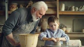 Att att bry sig farfadern är att hålla ögonen på hans barnbarnstöpningslera på att kasta hjulet som gör den låga keramiska vasen  stock video