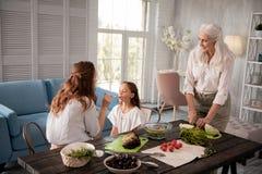 Att bry sig farmodern som håller ögonen på hennes dotter och sondotter Royaltyfria Bilder
