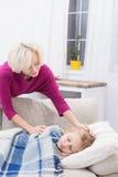 Att bry sig mamman som smeker hennes lilla sömniga sjuka barn royaltyfri foto