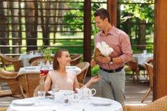 Att att bry sig mannen som känner upphetsat framlägga, blommar till flickvännen Royaltyfri Fotografi