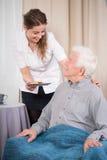 Att bry sig sjuksköterskan och äldre man Royaltyfria Foton