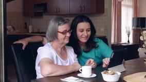 Att bry sig sjuksköterskan som visar en digital minnestavla till en äldre kvinna i ett vårdhem arkivfilmer