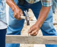 Att bulta för arbetare spikar in i trä arkivfoton