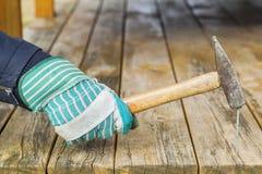 Att bulta för arbetare spikar i träbräde Royaltyfri Fotografi