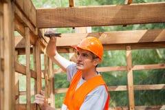 Att bulta för arbetare spikar på träkabinen fotografering för bildbyråer