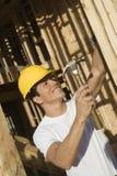Att bulta för arbetare spikar på träväggen arkivbild