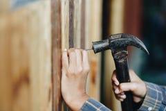 Att bulta för ung kvinna spikar i vägg arkivfoto