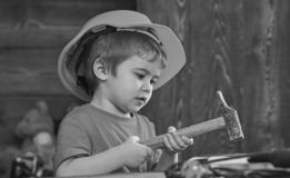 Att bulta för ungepojke spikar in i träbräde Barn, i gulligt spela för hjälm som byggmästare eller reparatör, att reparera eller  arkivfoton