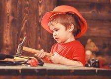Att bulta för ungepojke spikar in i träbräde Barn, i gulligt spela för hjälm som byggmästare eller reparatör, att reparera eller  royaltyfri foto