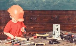 Att bulta för ungepojke spikar in i träbräde Barn i gulligt spela för för stor hjälm som byggmästaren eller reparatören som repar arkivfoto