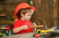 Att bulta för ungepojke spikar in i träbräde Handcrafting begrepp Lilla barnet på upptagen framsida spelar hemma i seminarium Bar royaltyfria foton