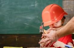 Att bulta för ungepojke spikar in i träbräde Lilla barnet på upptagen framsida spelar hemma i seminarium ny expertis för begrepp  arkivfoton
